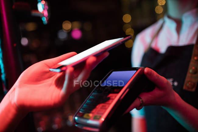 Client d'effectuer le paiement par l'intermédiaire de téléphone intelligent en bar — Photo de stock