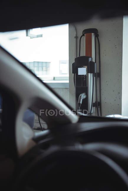 Macchina elettrica a innesto vista attraverso il parabrezza dell'auto presso la stazione di ricarica del veicolo elettrico — Foto stock