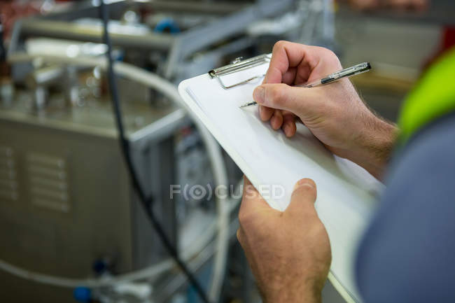 Close-up of technician examining machine at factory — Stock Photo