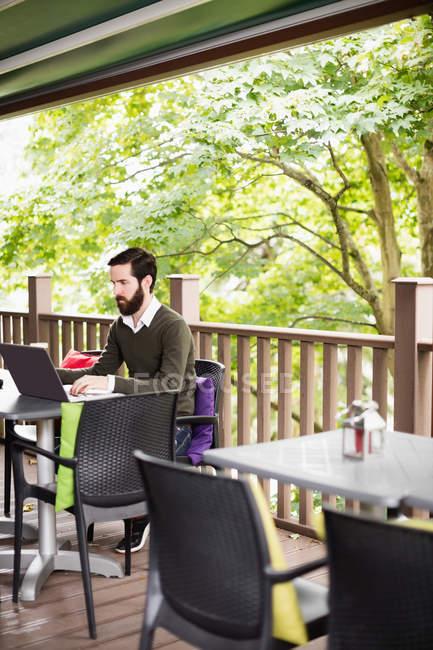 Mann mit Laptop in bar Terrasse — Stockfoto