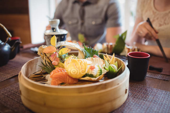 Close-up of various sushi in restaurant and couple in background — Stock Photo