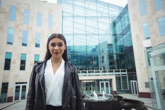 Портрет женщины, стоящей возле офисного здания — стоковое фото