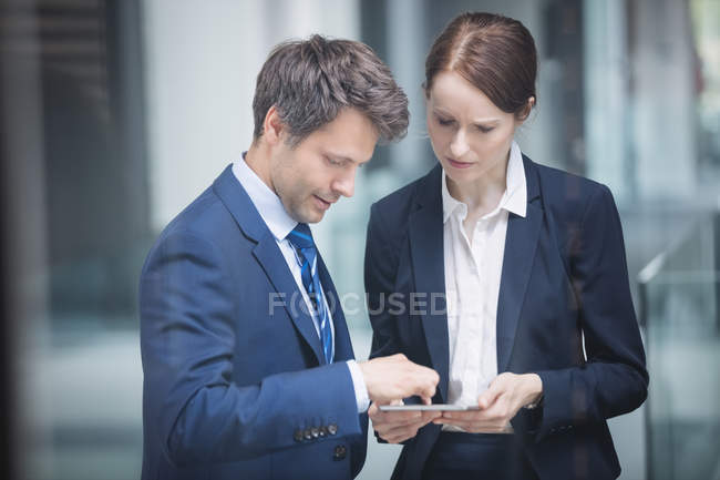 Businessman and colleague discussing over digital tablet inside office building — Stock Photo