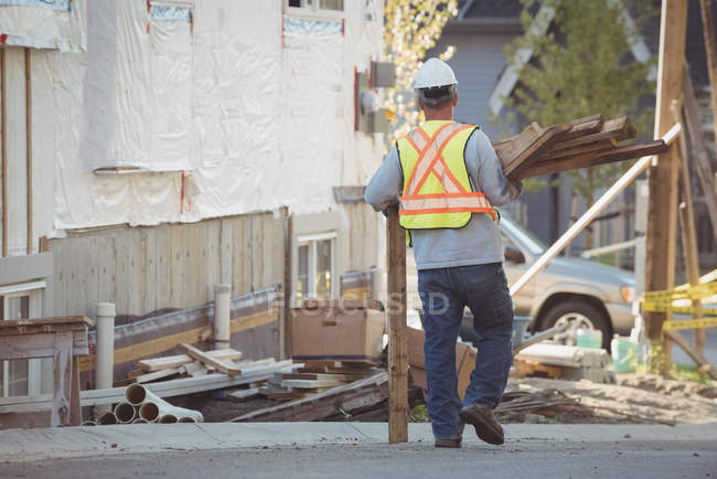 Rear view of construction worker carrying timber at construction site — Stock Photo