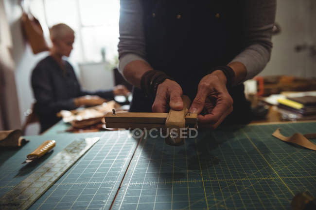 Mid-section of craftswoman preparing leather belt — Stock Photo