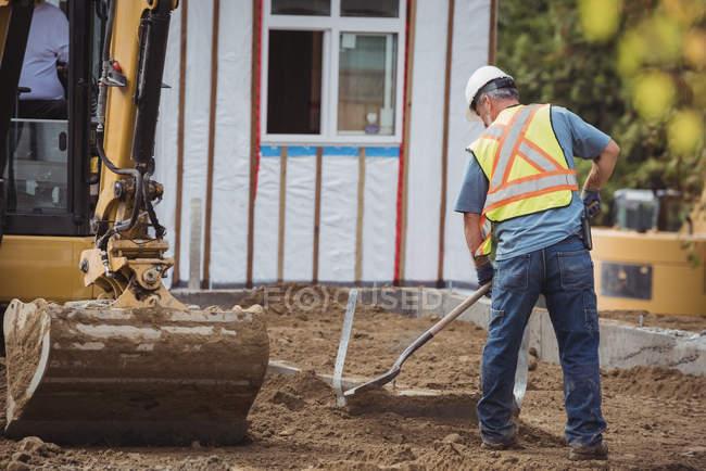 Працівник будівництва вирівнювання бруду на будмайданчик — стокове фото