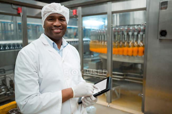 Портрет работника мужского пола с цифровым планшетом во время осмотра бутылок с соком на заводе — стоковое фото
