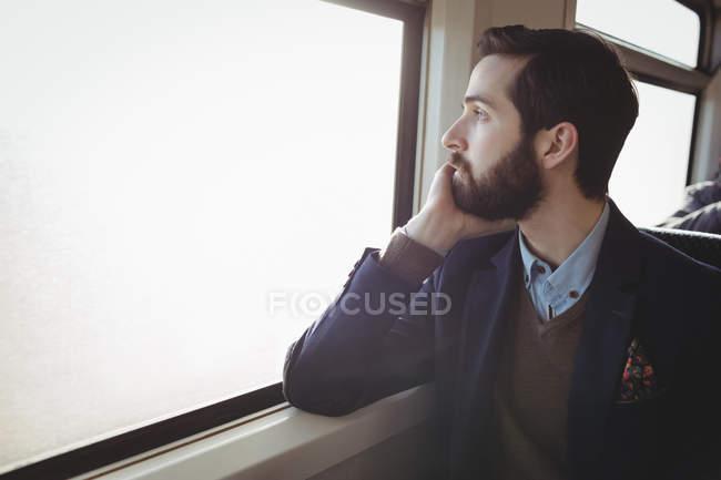 Homem de negócios atencioso olhando através da janela no trem — Fotografia de Stock