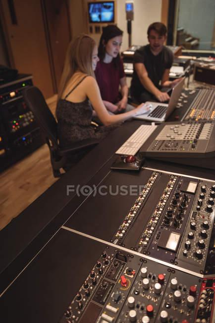 Аудиоинженеры используют ноутбук рядом с миксером звука в музыкальной студии — стоковое фото