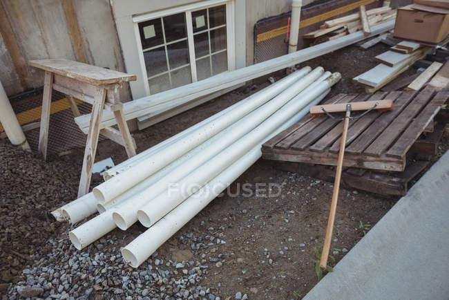 Пластиковые трубы и деревянные доски на строительной площадке — стоковое фото