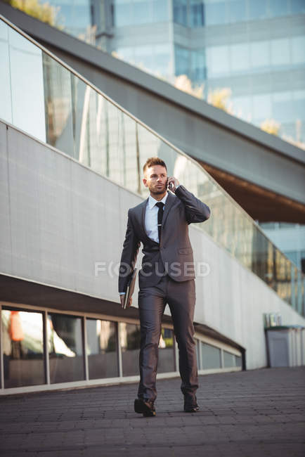 Businessman with a diary talking on mobile phone in the office campus — Stock Photo
