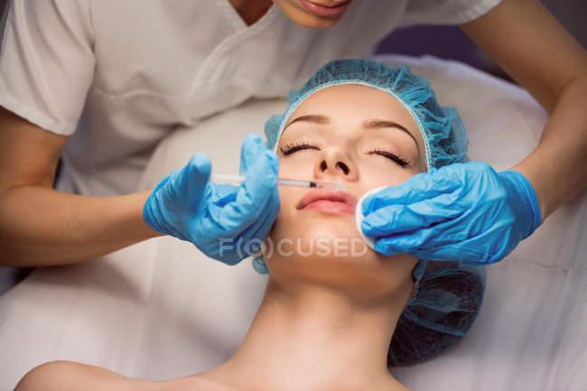 Крупным планом женщина-врач делать инъекции лицо молодой женщине в клинике — стоковое фото