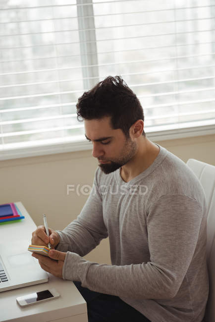Handsome man writing on sticky notes at home — Stock Photo