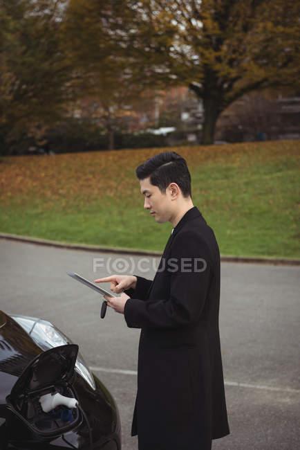 Homme à l'aide de tablette numérique tout en chargeant la voiture électrique à charge conductive pour véhicules électriques — Photo de stock
