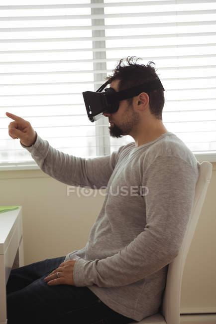 Visão lateral do homem usando headset realidade virtual enquanto sentado na mesa — Fotografia de Stock