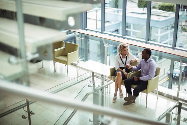 Бизнес-руководители, взаимодействующие в коридоре в офисе — стоковое фото