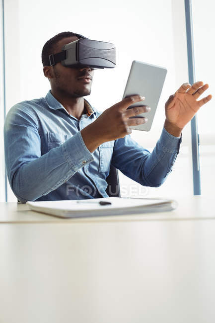 Business executive using virtual reality headset and digital tablet in office — Stock Photo