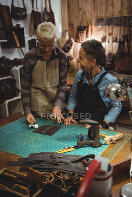 Craftswomen discussing over a piece of leather in workshop — Stock Photo