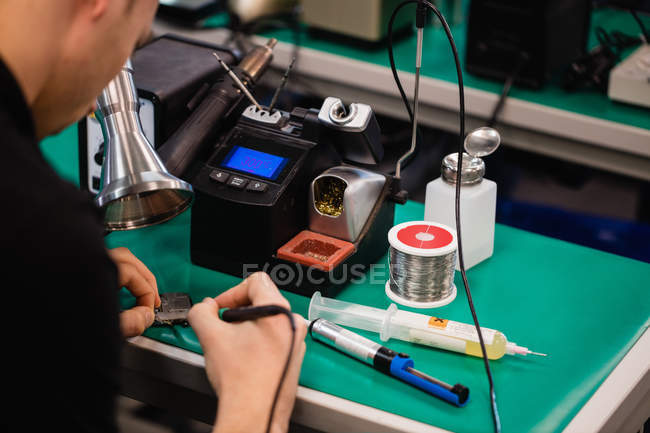 Man repairing an electronic device using soldering iron in service centre — Stock Photo