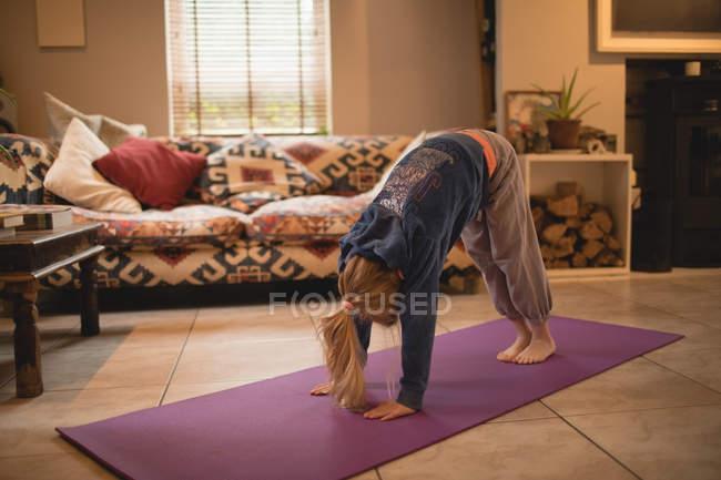 Девушка, занимающаяся йогой в гостиной дома — стоковое фото