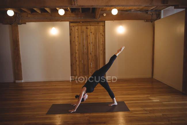 Жінка робити вправи при заняттях йогою в фітнес-студія — стокове фото