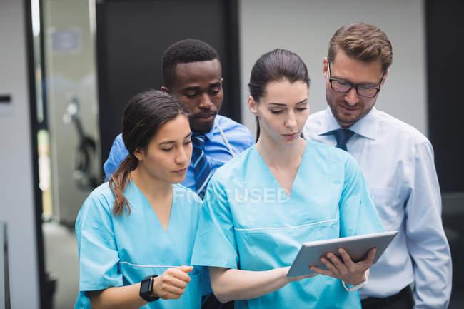 Equipe médica discutindo sobre tablet digital no corredor do hospital — Fotografia de Stock