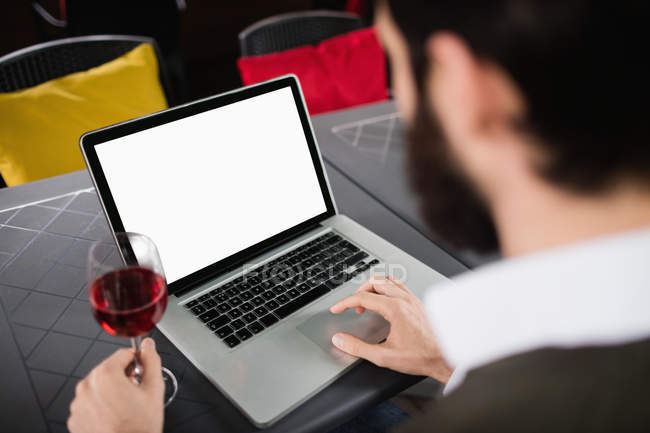 Man using laptop while having glass of wine in bar — Stock Photo