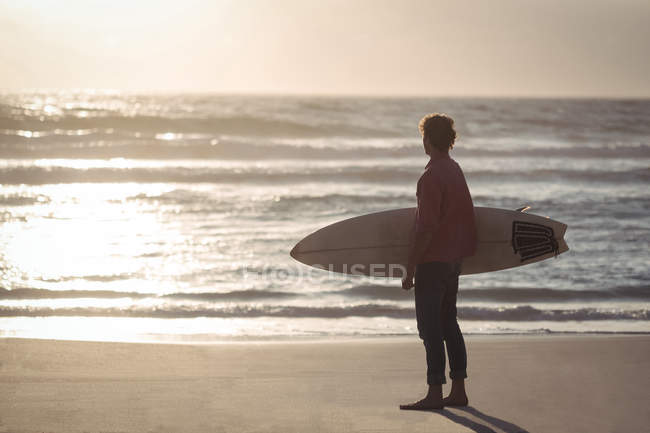 Man carrying surfboard standing on beach at dusk — Stock Photo