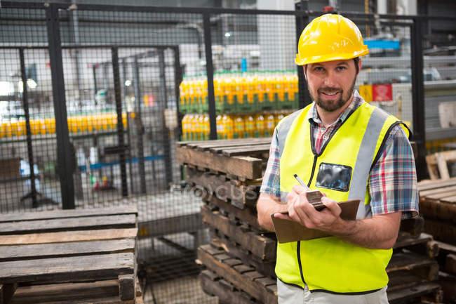 Porträt eines lächelnden männlichen Arbeiters, der über Produkte im Lager schreibt — Stockfoto