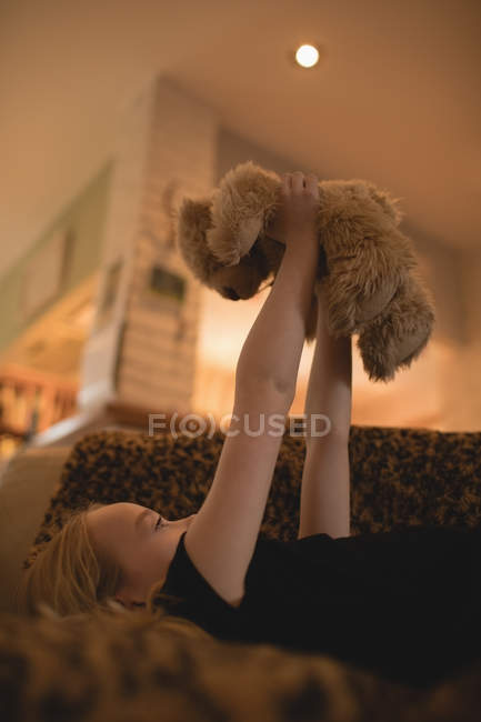 Girl lying on sofa and playing with teddy bear in living room at home — Stock Photo