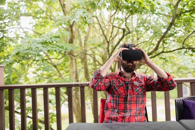 Young man using virtual reality headset in outdoor terrace — Stock Photo