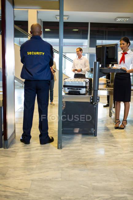 Guardia de seguridad del aeropuerto con pasajeros caminando a través del escáner corporal en la terminal del aeropuerto - foto de stock