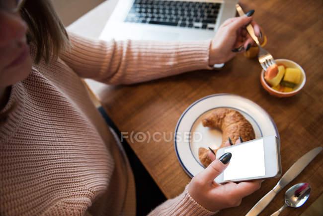 Donna che usa il telefono cellulare mentre fa colazione in soggiorno a casa — Foto stock