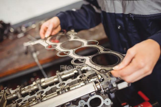 Mittleren Teil des weiblichen Mechaniker überprüfen Autoteile in Werkstatt — Stockfoto