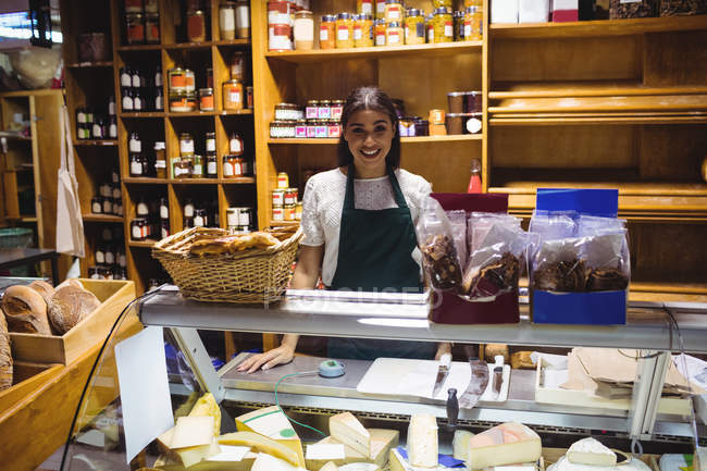 Female staff standing at cheese counter in supermarket — Stock Photo