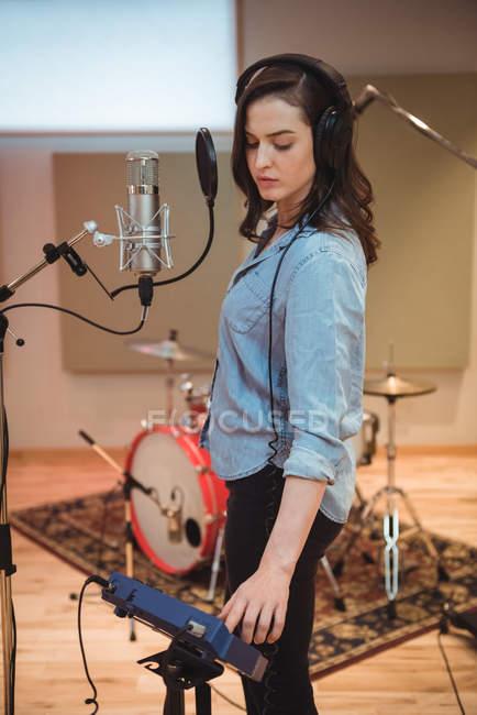 Женщина регулирует громкость во время пения в музыкальной студии — стоковое фото