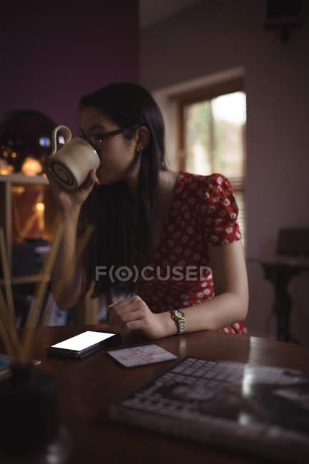 Frau trinkt Kaffee am Tisch im Haus — Stockfoto