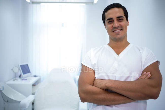 Portrait of male dentist standing with arms crossed in dental clinic — Stock Photo