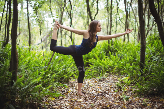 Woman performing standing bow pose yoga in forest on a sunny day — Stock Photo