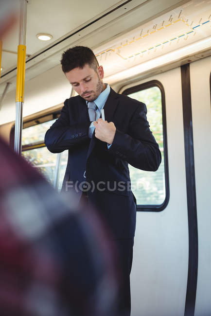Businessman checking blazer pocket while travelling in train — Stock Photo