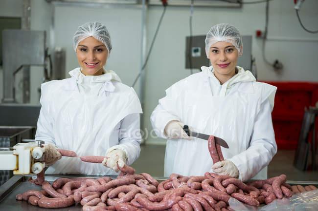 Портрет усміхнене жіночий м'ясників, різання ковбас — стокове фото