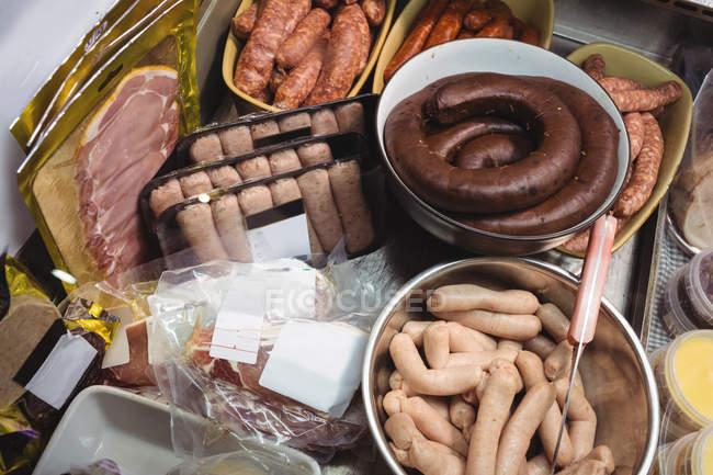 Varios tipos de salchichas y salami en el supermercado - foto de stock