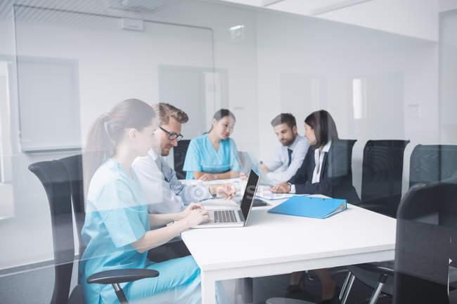 Médicos discutindo sobre laptop em reunião na sala de conferências — Fotografia de Stock