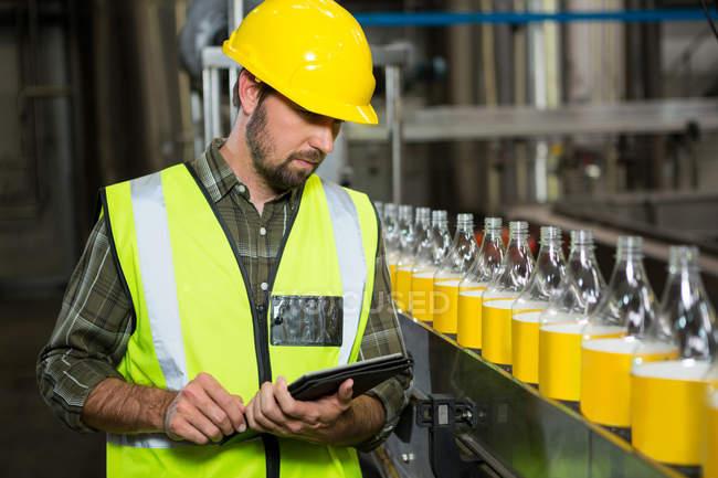 Серьезный работник мужчина с помощью цифровых таблеток на соковом заводе — стоковое фото
