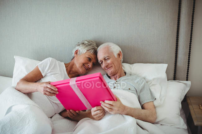 Senior man presenting gift to senior women on bed in bed room — Stock Photo