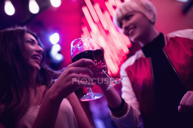 Smiling friends toasting wine glasses in bar — Stock Photo