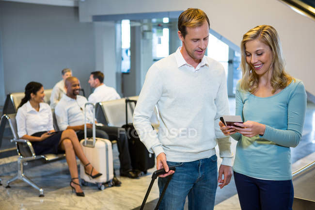 Couple standing with luggage holding smartphone and boarding pass in waiting area — Stock Photo