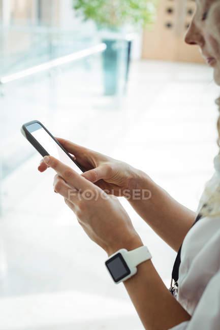 Close-up de empresária usando telefone celular no corredor do escritório — Fotografia de Stock
