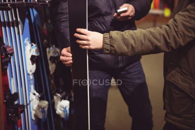 Primo piano della coppia che sceglie lo sci insieme in un negozio — Foto stock
