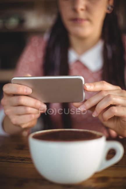 Жінка користується мобільним телефоном у кафе. — стокове фото